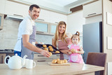 A happy family prepares baking in the kitchen
