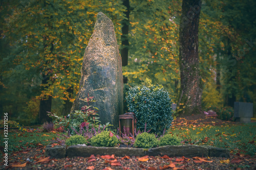 Close-up photo of a grave on a sunny autumn day in a forest