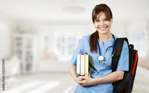 Leinwanddruck Bild Attractive young female doctor student on background
