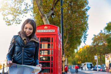 Attraktive Touristin in London vor einer roten Telefonzelle schaut auf einen Stadtplan