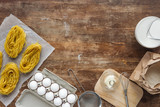 top view of uncooked pasta and raw ingredients on wooden table - 232288247
