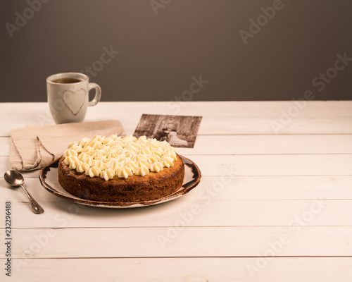 Poster a homemade dessert of carrot cake topped with cream cheese frosting, on white wooden backdrop, grey background