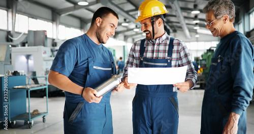 Leinwanddruck Bild Team Of Engineers Having Discussion In Factory