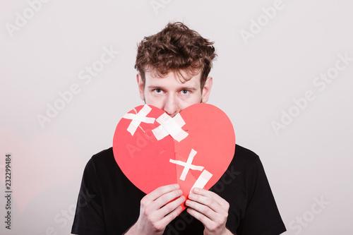 Leinwanddruck Bild Sad man with glued heart by plaster.