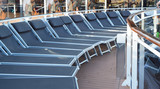 Empty sunbeds lounge chairs for relaxing on the open deck of a cruise ship - 232304099