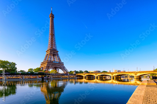 Leinwanddruck Bild View of Eiffel Tower and river Seine at sunrise in Paris, France. Eiffel Tower is one of the most iconic landmarks of Paris