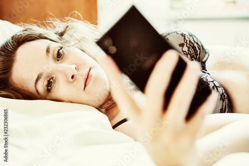 fototapeta na ścianę sinnliche junge Frau liegt in Unterwäsche mit ihrem Smartphone in der Hand auf dem Bett, Köln, Nordrhein-Westfalen, Deutschland