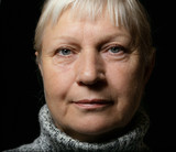 Middle aged woman portrait in sweater on dark background. - 232307495
