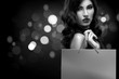 Quadro Christmas or Black friday sale concept. Shopping woman holding bag on dark background with bokeh in holiday. BW photo.