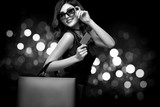 Christmas or Black friday sale concept. Shopping woman holding bag on dark background with bokeh in holiday. BW photo. - 232317625