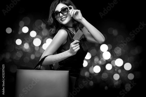 Boże Narodzenie lub czarny piątek koncepcja sprzedaży. Zakupy kobiety mienia torba na ciemnym tle z bokeh w wakacje. Zdjęcie BW.