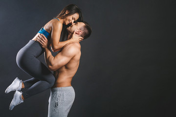 Happy smiling sporty young sexy couple isolated over black background.