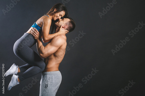 Wall mural Happy smiling sporty young sexy couple isolated over black background.