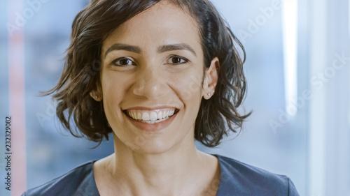 Leinwanddruck Bild Portrait of a Beautiful Hispanic Woman Smiling Charmingly Stepping into Focus.