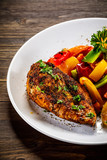 Grilled chicken fillet and vegetables on woowde table - 232332463