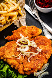 Fried pork chop, French fries and vegetables on wooden background - 232333297