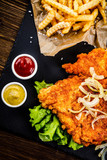 Fried pork chop, French fries and vegetables on wooden background - 232333453