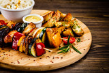 Kebab - grilled meat and vegetables on cutting board on wooden table - 232333853