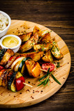 Kebab - grilled meat and vegetables on cutting board on wooden table - 232334045