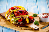 Tacos on cutting board on wooden table - 232334420