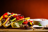 Tacos on cutting board on wooden table - 232334489