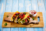 Tacos on cutting board on wooden table - 232334601
