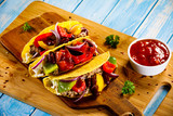 Tacos on cutting board on wooden table - 232334670