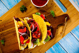 Tacos on cutting board on wooden table - 232334874