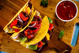 Tacos on cutting board on wooden table - 232335054