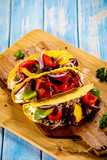 Tacos on cutting board on wooden table - 232335252