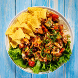 Grilled chicken meat with nachos and vegetables on wooden background - 232335872