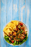 Grilled chicken meat with nachos and vegetables on wooden background - 232336019
