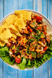 Grilled chicken meat with nachos and vegetables on wooden background - 232336090