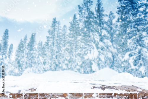 Wall mural Snowing over forest pine trees and brown wooden deck