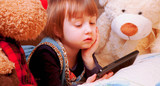 Cute llittle girl using mobile phone with teddy bear in the bedroom before bedtime. (relaxation, education, sleep, technology concept) - 232386614