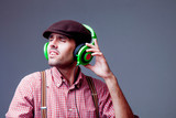 Handsome man dj with closed eyes in fashionable retro styled wear and headphones listening to the music. Party, music, relax concept. - 232388264