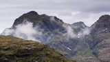 Clouds pass by a mountaintop on the Lofoten islands, Norway. - 232389028