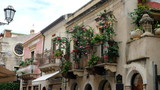 Taormina, Province of Messina, Sicily. All around the city there are beatiful balconies, often decorated with flower pots. This is Corso Umberto, the main street of the city. - 232394075