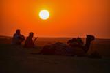 インドのラジャスタン州 ジャイサルメールのクーリー村の砂漠 美しい夕日と砂漠 休憩中のラクダとラクダ使いの男