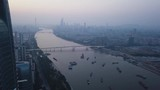 Aerial shot of Pazhou area of Guangzhou with office building, pearl river, and boats anchored and city downtown in the distance - 232397612
