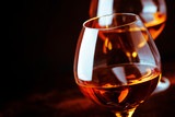 Grape brandy in shot glass, dark brown background, selective focus - 232402227