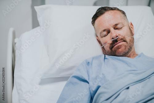 Leinwanddruck Bild Sick man in a hospital bed