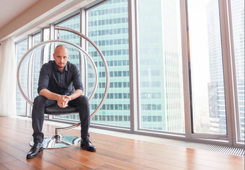 Young attractive stylish bald man in a business suit in his office in a skyscraper, business, finance, success