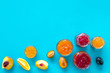 Jams different tastes made of fruits and berries near pieces of fruits on blue background top view copy space