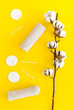 Leinwanddruck Bild - Cotton hygiene products. Cotton pads and swabs, towels twisted coil near dry cotton flowers on yellow background top view