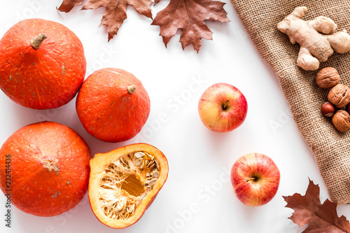 Autumn garden harvest. Dried leaves, pumpkin, apple, tomatoes, ginger and nuts on white background top view