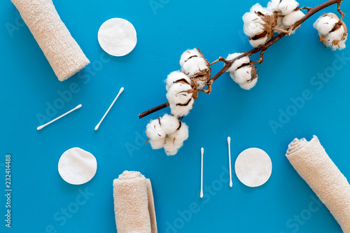 Leinwanddruck Bild Products made of cotton. Bath accessories. Towels, cotton pads and swabs near dry cotton flowers on blue background top view