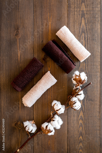 Leinwanddruck Bild Cotton towels high quality. Set of towels twisted coil near dry cotton flowers on dark wooden background top view copy space