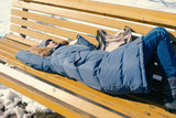 Tired young woman sleeps in the Park on a bench in the winter. - 232419255