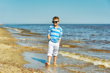 A boy on a walk along the sea coast . Child in white trousers and t-shirt